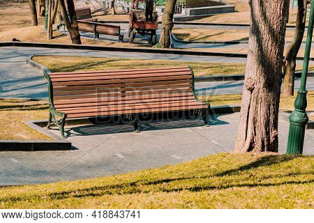 Empty Brown Wooden Bench With A Decorative Ornate Metal Legs And Armrests Installed In Levels Park W
