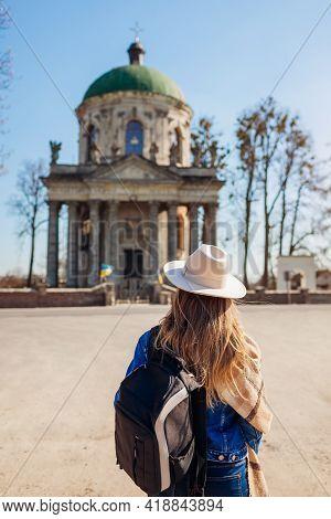 Tourist Looking At Ancient Roman Catholic Church Of Saint Joseph In Pidhirtsi, Ukraine. Visiting Anc