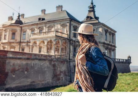 Tourist Woman Enjoys View Of Castle In Pidhirtsi. Travel To Historic Places Of Interest, Ancient Arc