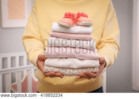 Woman Holding Stack Of Girl's Clothes And Booties Indoors, Closeup