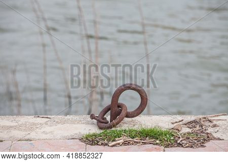 Selective Blur On A Rusty Boat Mooring Ring On A Quay, A Wharf Pier By A River Next To The Sea, Used