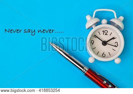 Top View Of Clock And Pen Over Blue Background Written With Never Say Never.