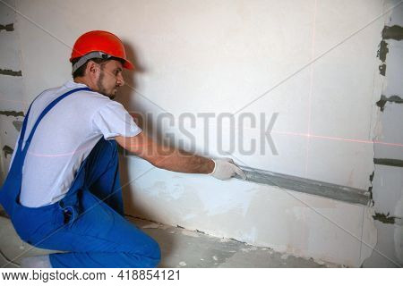 Work On Finishing The Walls With Mixtures Of Plaster And Putty When Building A House. Builder Worker