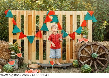 Adorable Kid Eat A Watermelon In The Backyard. Cute Little Boy Eating Watermelon In The Summer Outdo