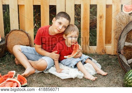 Kids Eat Fruit Outdoors. Healthy Snack. Happy Family Eating Watermelon In The Garden. Two Little Cut