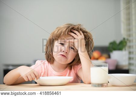 Unhappy Child Sit At Table At Home Kitchen Have No Appetite. Caucasian Toddler Child Boy Eating Heal