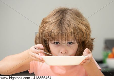 Child Eat. Little Healthy Hungry Boy Eating Soup With Spoon. Cute Curious Hungry Funny Kid.
