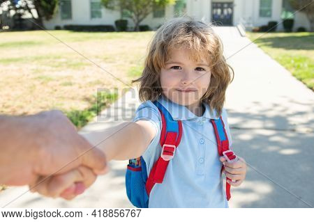 Little Boy With Backpack Holding Parent Fathers Hand On Blurred School Building Background. Child Wi