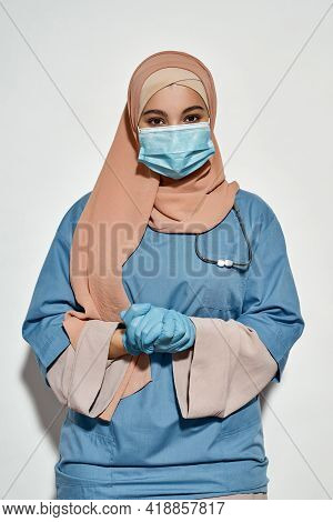 Young Arabian Girl Doctor With Stethoscope And Protective Mask Looking At Camera While Posing On Lig