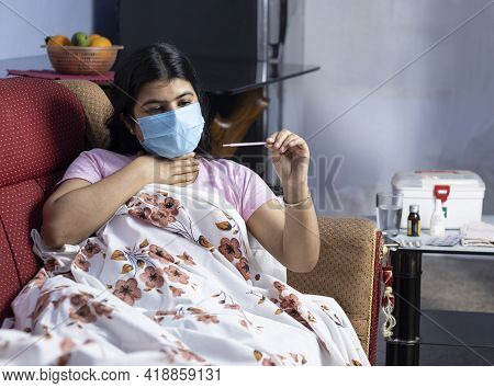 A Mid Adult Indian Woman Wearing Surgical Nose Mask Checking Body Temperature With A Thermometer, Ly