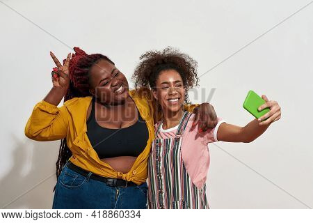 Two Afro Women Of Different Size Making Selfie And Posing, One Of Them Has Afro-tales Other Is Curly