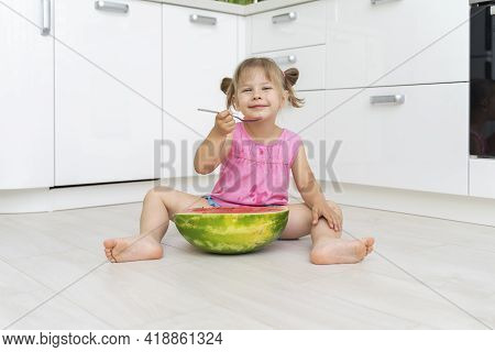 Playful Child Girl Eating Watermelon With Appetite With A Large Spoon Sitting On The Floor In A Whit