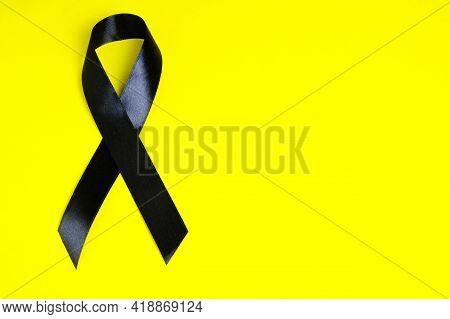 Black Ribbon On Yellow Background Is Symbol Melanoma, Symbol Of Memory Victims Stalinism And Nazism