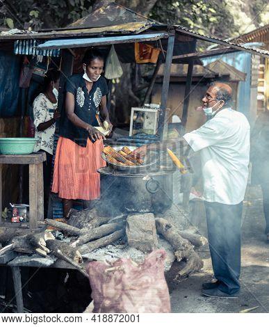 Ella, Sri Lanka - 04 15 2021: Buying Street Foods Near Rawana Ella From A Local Lady Vendor By A Man
