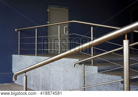 Porch steps and metal railing in front of closed door of entrance in modern building.