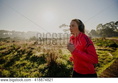 Caucasian Teen Athlete Jogging On Path In Luscious Forest Park