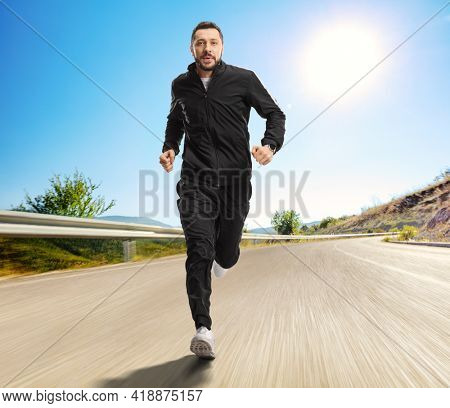 Full length portrait of a man in black tracksuits running on an open road