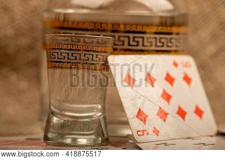 Playing Cards, A Glass Of Vodka And A Decanter Of Vodka On A Table Covered With Coarse Burlap. Close