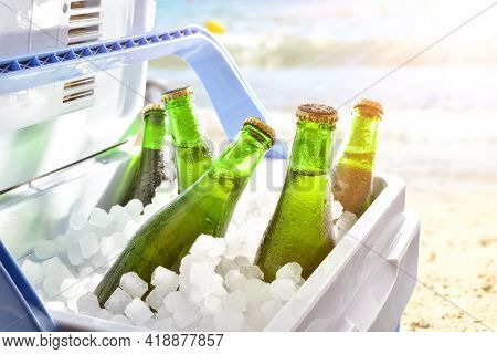 Bottles Of Beer Chilled On Ice In A Camping Fridge On A Beach On A Hot Day With Sunshine.