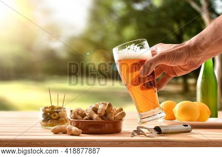 Man Having A Snack In The Countryside With A Glass Of Beer In Hand And A Table Full Of Snacks