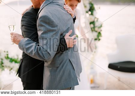 The Groom And The Best Man Hug During The Wedding Ceremony, The Bride Is Standing Nearby