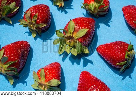 Top View Of Several Red Strawberries With Green Leaves On A Blue Background.healthy Food Concept.