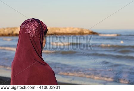 Young Girl With The Arab Headscarf To Cover Her Head By The Sea Awaits The Arrival Of Friends On The