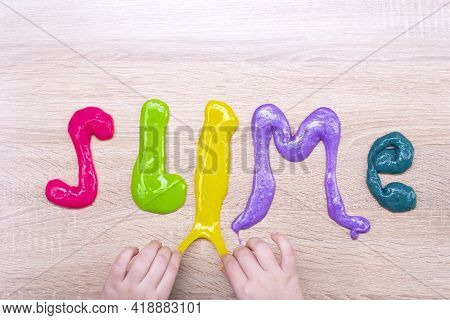 The Word Slime Made From Multi-colored Slimes On A Wooden Table. Slime Text Made Of Colored Slime On