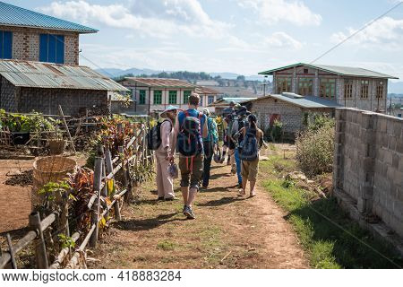 Shan State, Myanmar - January 6 2020: A Tourist Group With Backpacks Hikes Into A Rural Farm Village