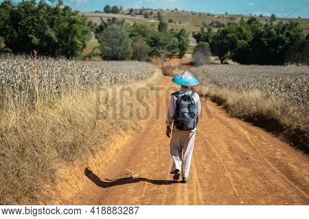 A Burmese Man In Traditional Clothing Walks Down A Dirt Road