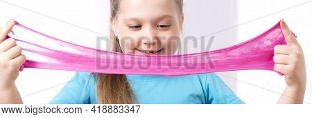 Blond Beautiful Caucasian Little Girl Is Playing With Slime And Smiling. Play A Slime Toy. Making Sl