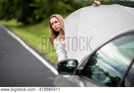 Pretty middle aged woman having car troubles - broken down car on the side of the road, calling the insurance company for assistance