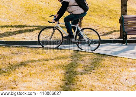Man On A Bicycle Going Uphill On An Angle Roadway Through The City's Park. Leisure. Sport. Urban. Mo