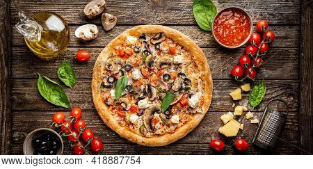 Tasty Vegetable Pizza And Cooking Ingredients Tomatoes And Basil On Wooden Background. Top View