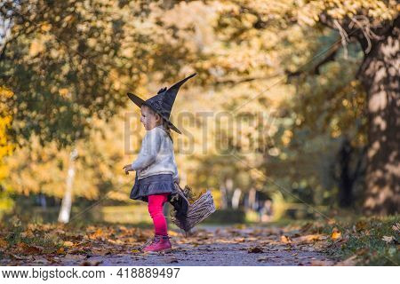 Adorable Little Toddler Girl Walking In Autumn Park. Girl In Witch Costume And Black Hat Cosplay Hal