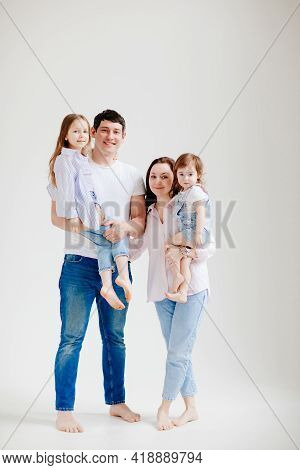 Beautiful Happy Family At A Photo Shoot In A White Photo Studio. Backstage.