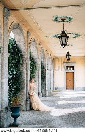Beautiful Bride In A Dress With A Bouquet Of Pink Flowers Is Leaning Against A Pillar In The Vaulted