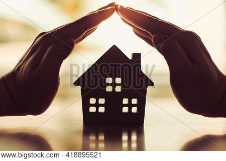 Real estate agents offer house, property insurance and security, affordable housing concepts. hands of a young woman surround a model of a wooden house