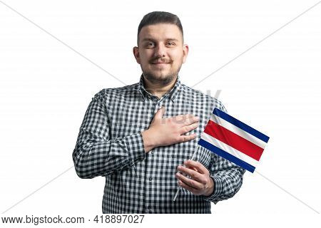 White Guy Holding A Flag Of Costa Rica And Holds His Hand On His Heart Isolated On A White Backgroun
