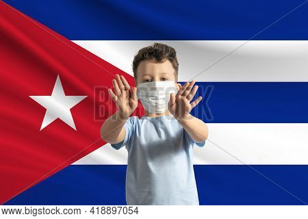 Little White Boy In A Protective Mask On The Background Of The Flag Of Cuba Makes A Stop Sign With H