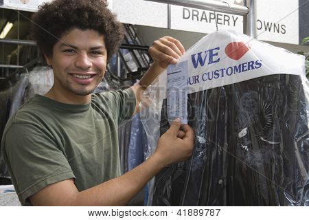 Portrait of young mixed race man holding receipt while standing by clothes rail