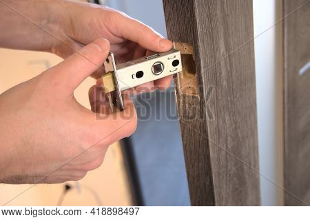 Insert Of Latch And Handle Into The Interior Door. Close-up View Of The Work Process.