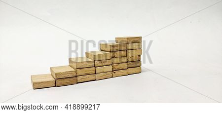 Closeup Of Stacked Wooden Blocks Made Like Step Or Ladder Pattern In A Isolated White Background Wit