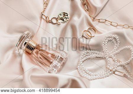 Women's Jewelry, Gold Chain, Trendy Jewelry, Perfume On A Silk Background.