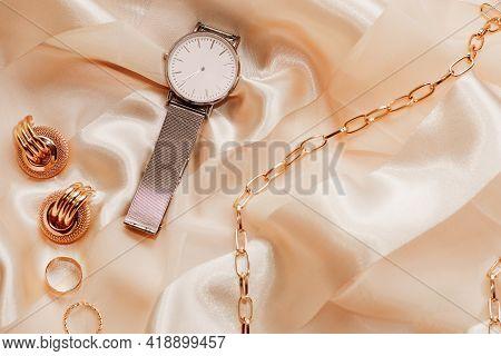 Women's Jewelry Earrings, Trendy Jewelry, Watches, Rings On A Silk Background.