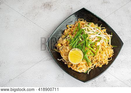 Pad Thai Served With Vegetables And Lemon Slices In Black Dish On Gray Cement Background. Thai Food
