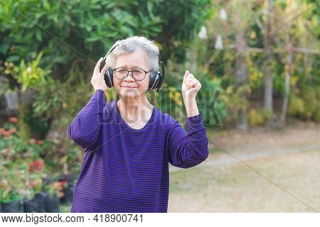 Asian Senior Woman Wearing Wireless Headphone Listening To A Favorite Song While Standing In A Garde