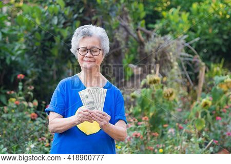 Portrait Of An Elderly Woman Holding $100 Amount Of $500 Dollars While Standing In A Garden. Selecti
