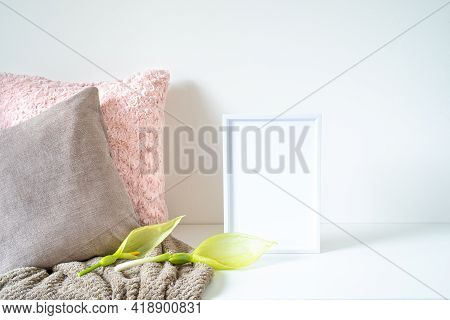 Empty White Frame Mockup On White Table. Soft Colored Cushions, Plaids And Arum Italicum Flowers. Mo