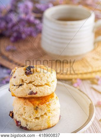 Side View Of Traditional English Scones On A Plate With A Tea Cup And Flower Blurred Background. Spa